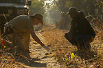 African Lion (Panthera leo) biologists, Jake Overton and Evans Nsende, collecing scat, Kafue National Park, Zambia