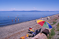 "People sunbathing on the Beach and wading and swimming in the Pacific Ocean at Qualicum Beach, in the ""Oceanside Region"" of Vancouver Island, British Columbia, Canada"