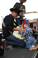 """MEGAN DAVIS/MCDONALD COUNTY PRESS 2-year-old Kayson Mart got his first taste of fame when Jason Young, of the Jason Young Band, taught Mart how to strum the guitar. The group performed a number of 90s hits for the Old Timer's Day crowd, as well as the Jason Young Band original """"Thank God For The Working Man."""""""