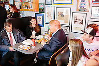 Republican presidential candidate Donald Trump sits with Press Secretary Hope Hicks and Campaign Manager Corey Lewandowski after speaking to reporters at the Red Arrow Diner in Manchester, New Hampshire.