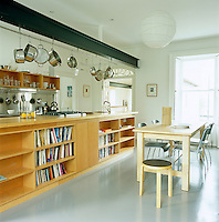 A long beech plywood island replaces the original kitchen wall with cupboards and appliances on one side and shelves on the other. The steel beam supporting the roof doubles as a utensil rack