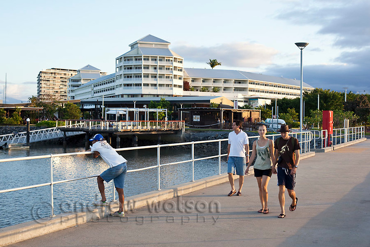 Tourists walking along Marlin Marina jetty with Shangri-La Hotel in background.  Cairns, Queensland, Australia