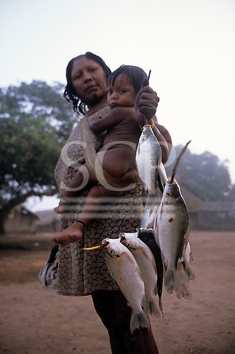 Bacaja village, Brazil. Indian mother carrying a child and holding fresh fish on a stick; Xicrin Indian tribe, Amazon.