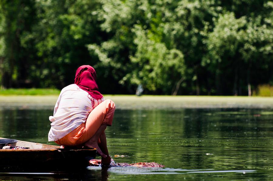 Kashmiri woman in headscarves washing laundry from their traditional shikara, Dal Lake, Srinagar, Kashmir, India.