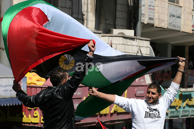 Palestinian demonstrators take part in a protest calling for Palestinian political unity between Gaza's Hamas rulers and the Fatah-dominated Palestinian Authority which rules from Ramallah, on March 15, 2011 in Ramallah, as Palestinian activists across the Gaza Strip and the West Bank stage a day of massive demonstrations to call for political unity. Photo by Issam Rimawi