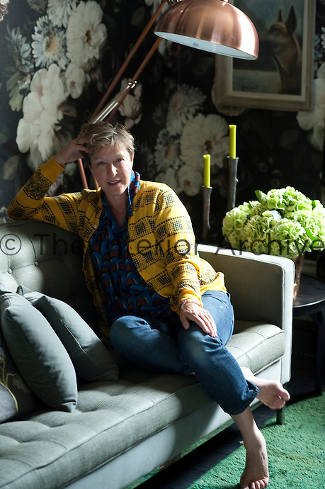 Florist, Nicky Tibbles, photographed in the living room of her Notting Hill home. The sofa is Knoll and the wallpaper was designed by Ellie Cashman