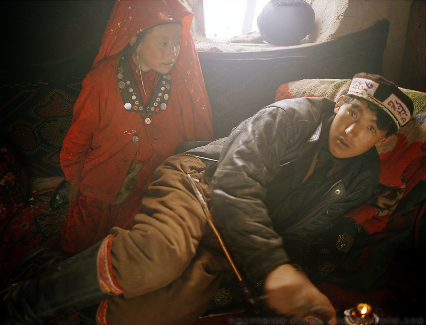 Noor Ullah smokes opium 3 times a day, each session is about 1 hour. His younger sister, Tella Bu, watches on..Opium users inside Ooroon Boi's house, son of the Khan. Winter expedition through the Wakhan Corridor and into the Afghan Pamir mountains, to document the life of the Afghan Kyrgyz tribe. January/February 2008. Afghanistan