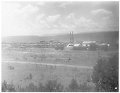 View from a distance of Continental Tie &amp; Lumber Company tie treating plant on right, lumber stacks on left and rear and railcars on sidings.<br /> Cimarron, NM  Taken by Newman, Almeron - 1900-1910