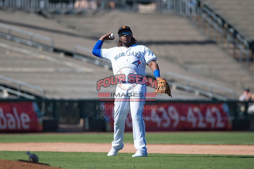 Surprise Saguaros third baseman Vladimir Guerrero Jr. (27), of the Toronto Blue Jays organization, prepares to make a throw to first base during an Arizona Fall League game against the Salt River Rafters on October 9, 2018 at Surprise Stadium in Surprise, Arizona. The Rafters defeated the Saguaros 10-8. (Zachary Lucy/Four Seam Images)