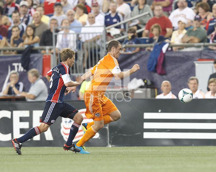 Houston Dynamo forward Cam Weaver (15) brings the ball forward as New England Revolution midfielder Scott Caldwell (6) closes. In a Major League Soccer (MLS) match, Houston Dynamo (orange) defeated the New England Revolution (blue), 2-1, at Gillette Stadium on July 13, 2013.