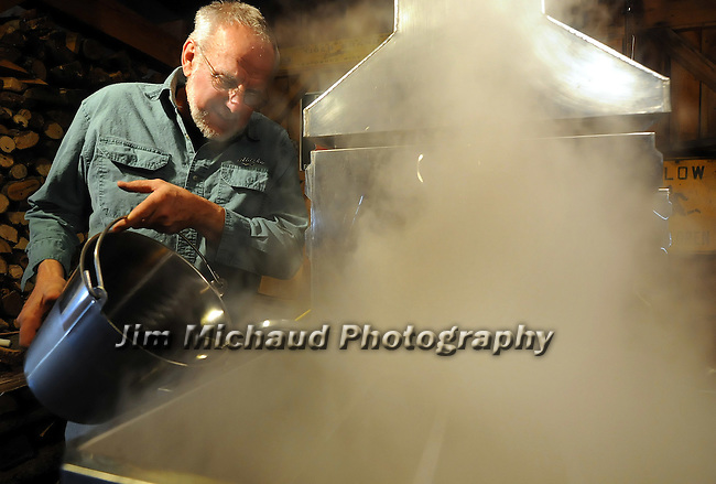 Russ Schaller, works adding some maple sap into the evaporator as he works at his small farm in Hebron, Wednesday, Feb. 22, 2012. Schaller collected 300 gallons of sap Wednesday that could yield 6 or more gallons of maple syrup. Schaller runs his Woody Acres Sugarhouse mostly as a hobby producing about 50 gallons of syrup a season he sells locally. (Jim Michaud/Journal Inquirer)