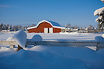 Idaho, Dalton Gardens, Coeur d' Alene. A red barn in a snowy landscape on a small farm.