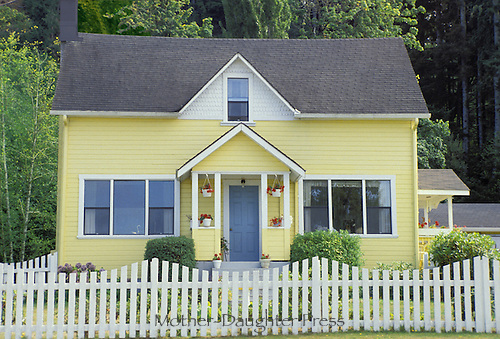 Yellow house with blue door and potted plants surrounded by picket fence, Astoria Oregon, USA