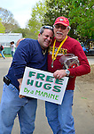 At right, Marine JOHN GIORDANA, of Whitestone, a Korean War Vet, gives a Free Hug to a smiling visitor at the Marine Corps League's booth collecting donations for veterans, at the Antique Auto Show on the farmhouse grounds of Queens County Farm Museum.