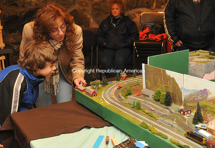 WINSTED, CT-11 FEBRUARY 2009-021110IP04-Lori Cesnak and her son Sam Cesnak, 8, of Winsted, and Rosie Foth (background) of Torrington, look at a tabletop railroad display by the Torrington Area Model Railroaders at Beardsley and Memorial Library in Winsted on Thursday. The display, built by Ed Sweeney of Winsted, is composed of modules that are snapped together.<br /> Irena Pastorello Republican-American
