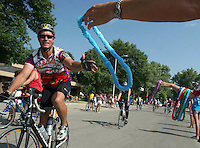 Riders are given leihs while riding into Laurens Monday morning on RAGBRAI XXXV.  The town had a tropical theme for the visiting riders.