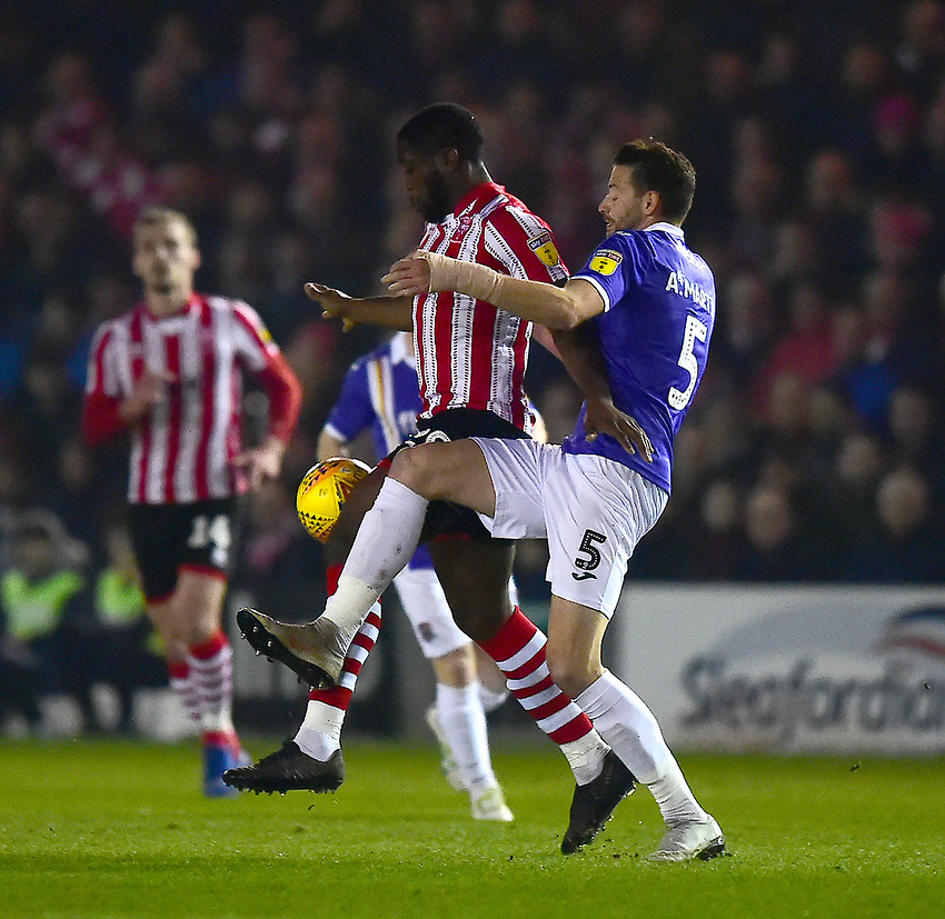 Lincoln City's John Akinde shields the ball from Exeter City's Aaron Martin<br /> <br /> Photographer Andrew Vaughan/CameraSport<br /> <br /> The EFL Sky Bet League Two - Lincoln City v Exeter City - Tuesday 26th February 2019 - Sincil Bank - Lincoln<br /> <br /> World Copyright © 2019 CameraSport. All rights reserved. 43 Linden Ave. Countesthorpe. Leicester. England. LE8 5PG - Tel: +44 (0) 116 277 4147 - admin@camerasport.com - www.camerasport.com