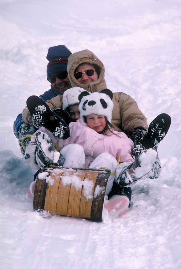 Winter scene.  A smiling family of mother, father and 2 children ride a sled down hill. Winter blizzards can be fun when the whole family is home to play on sleds in the snow. Bethesda Maryland.