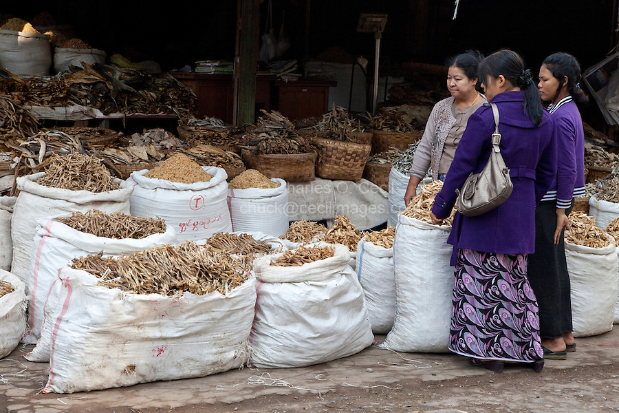 Myanmar, Burma.  Mandalay.  Women Examining Choices in the Dried Fish Market.