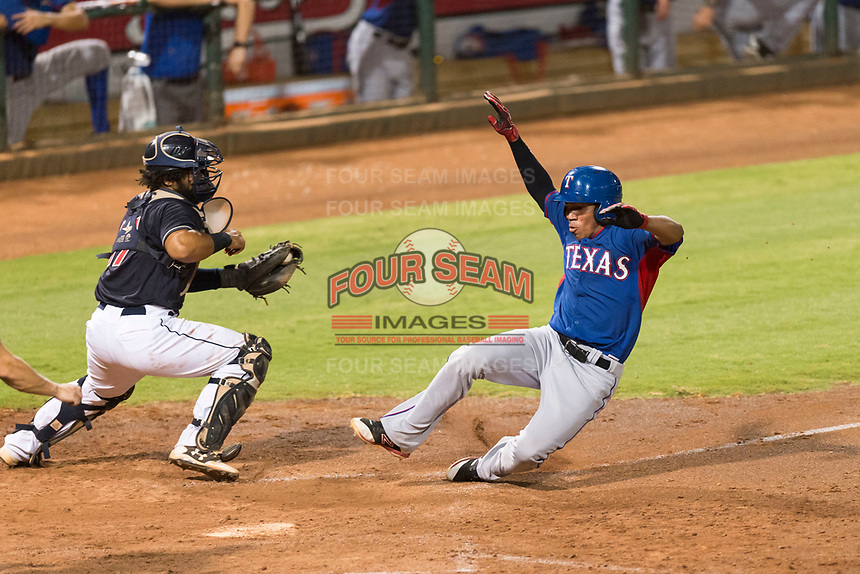 AZL Rangers pinch runner Yenci Pena (18) slides to avoid the tag by catcher Felix Fernandez (17) during an Arizona League playoff game against the AZL Indians 1 at Goodyear Ballpark on August 28, 2018 in Goodyear, Arizona. The AZL Rangers defeated the AZL Indians 1 7-4. (Zachary Lucy/Four Seam Images)