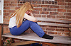 Teenage girl sitting outside on bench holding head in hands,