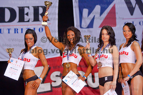 Competitor Rita Kovari (2nd L) winner of the under 165 cm category celebrates her victory with Mariann Szigeti-Tarr (L) during the Miss Zsaru (Miss Cop) contest in Budapest, Hungary on May 13, 2012. ATTILA VOLGYI
