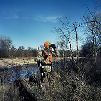 OutdoorLife Editor Andrew McKean (cq) looks for white tail deer through binoculars during a hunt in Superior, Nebraska, Friday, December 2, 2011. ..Photo by Matt Nager