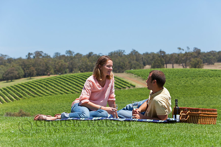 Couple having a picnic with a vineyard in the background.  Montgomerys Hill Winery, Albany, Western Australia, Australia