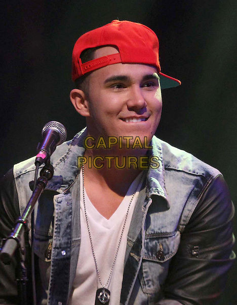 1 April 2013 - Los Angeles, California - Carlos Pena, Jr of Big Time Rush. BIG TIME RUSH Big tour Announcement and Performance Held At The House Of Blues.  .on stage in concert live gig performance performing music headshot portrait jean denim jacket red baseball cap hat.CAP/ADM/KB.©Kevan Brooks/AdMedia/Capital Pictures.