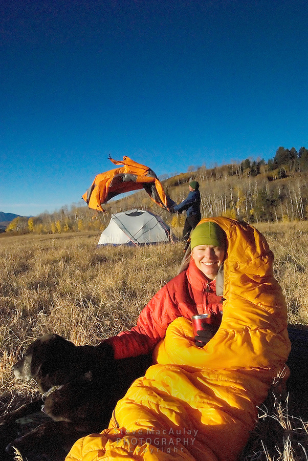 Young woman with dog, wrapped up in orange sleeping bag, holding coffee mug at sunrise at campsite,Male camper setting up tent fly in background. Fall, Grand Teton National Park, Wyoming