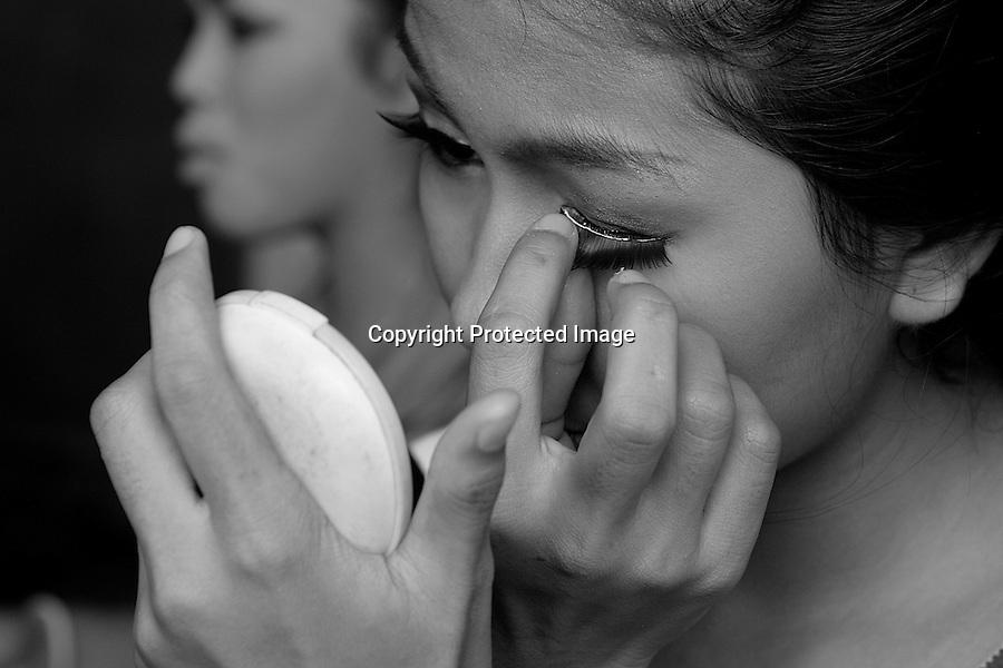 Children of Bassac. Kong Chandamony, nickname Chenda, is putting on fake eyelashes. Phnom Penh, Cambodia - 2007