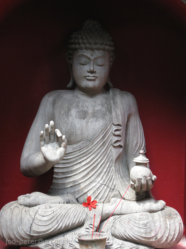 Buddha stone sculpture with red Hibiscus flower and red wall, Bali, archipelago Indonesia