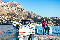 A woman waiting for the ferry boat connecting Kalymnos with Telendos, while on a winter climbing trip in Greece.