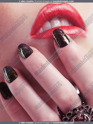 Closeup of a woman hand with fancy sparkling nail polish touching her red lips