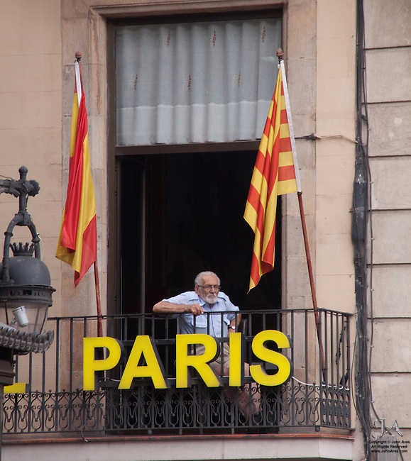 Old man on balcony wathing the crowds on Las Ramblas, Barcelona Spain.  Flanked by colorful flags behind, he sits in front of a sign for the PARIS hotel.  He is no where near Paris.  Another sign of Globalization