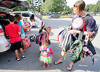 NWA Democrat-Gazette/DAVID GOTTSCHALK Lynette Washington (right to left) unloads backpacks with her daughter Chloe, 2, and Lydia, 4, volunteer Taylor Ellis-Watson, daughter Maiesha, 8, and son Jeremiah, 10,before they carry the donated backpacks filled with school supplies into Asbell Elementary School Monday, August 3, 2015 in Fayetteville. The group is participating in The Grove Church's fourth annual Packs for Life program which collects and donates age specific school supplies. Asbell Elementary School begins today.