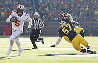 Ohio State Buckeyes quarterback Braxton Miller (5) gets past Michigan Wolverines defensive end Frank Clark (57) and Michigan Wolverines defensive tackle Willie Henry (69) for a second quarter TD at Michigan Stadium in Ann Arbor, MI on November 30, 2013.  (Chris Russell/Dispatch Photo)