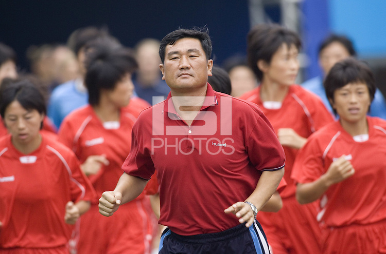 North Korea head coach Kim Kwang-Min leads his team out to the field before their first round game. The United States (USA) and North Korea (PRK) played to a 2-2 tie during a FIFA Women's World Cup China 2007 opening round Group B match at Chengdu Sports Center Stadium, Chengdu, China, on September 11, 2007.