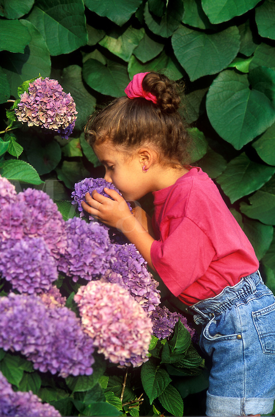 Little girl sniffing flowers.