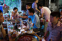 People eat at at Gang Shan Zha Zha, a popular streetside hotpot restaurant on Tiyu Road in central Yuzhong distrist, Chongqing, China. This group at the end of a table is eating from one of Chongqing's well-known 9-section hotpot bowls. They live in the neighborhood but it's the first time they've been to the restaurant because the line is usually too long. Their favorite ingredients of the night were cow stomach, cow intestine, and duck intestine. Xiao Feng (girl at the end of the table) said &quot;We [Chongqingers] like hot food, but this is very spicy for us.&quot;<br /> <br /> The restaurant sits on the site of a former neighborhood garbage collection point and &quot;zha zha&quot; is local slang for &quot;garbage.&quot; The restaurant has been open for 5 years and recently opened a second location elsewhere in Chongqing. A manager of the restaurant said that they server 60-70 tables every night, with many tables' bills coming to over 1000RMB. The restaurant often has a long wait. The site is well-reviewed on online restaurant sites similar to Yelp and is known for having good flavor, serving fresh food, and being clean.
