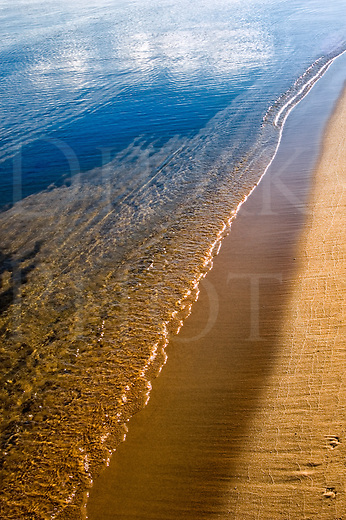 Long line of a small rolling wave on a beach at sunset. taken at Manistique, Michigan, in the Upper Peninsula.