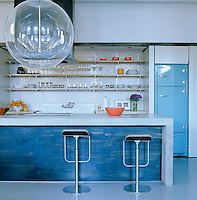 This kitchen has a retro feel with a mosaic backsplash, large enamel sink and pale blue fridge