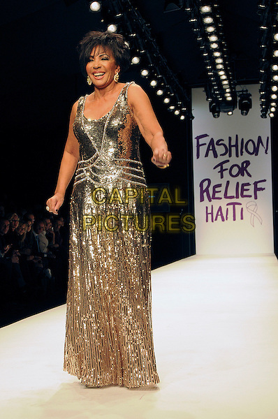 DAME SHIRLEY BASSEY.The Fashion For Relief Haiti 2010 show for London Fashion Week Autumn/Winter 2010 at Somerset House, London, England..February 18th, 2010.LFW catwalk runway full length silver gold maxi dress sequins sequined .CAP/CAS.©Bob Cass/Capital Pictures.