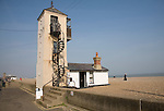 Old lookout Coastguard tower on the beach, Aldeburgh, Suffolk, England. This is the southern one of two lookout towers in the town. Rival pilotage companies used the towers to compete to be the first to spot approaching ships that would need to be guided inshore up the River Alde. The northern tower is just visible in the background.