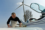 Jaap van der Beek checks the fuel of his airplane in Middenmeer, the Netherlands...Jaap van der Beek, pilot, wind farmer and farmer in Middenmeer, Holland. Mr. van der Beek owns one windmill on his property. Sensitive to recent decisions to try and group wind mills together from a government level, van der Beek is currently working with other wind mill owners in North Holland to secure a location for a collection of windmills. Until that time, van der Beek will continue to fly his plane and farm his tulips as the windmill powers him and hundreds of other homes.