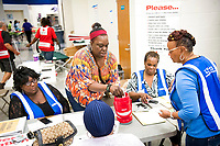 Social Service workers help an evacuee with her medications at a storm shelter at Ridge View High School as Hurricane Florence slowly moves across the the East Coast Friday, Sept. 14, 2018, in Columbia, S.C. (AP Photo/Sean Rayford)