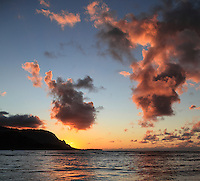 A distant standup paddler and others enjoy Hanalei Bay, with the remnants of sunset lighting both clouds and bay waters off of Kaua'i.