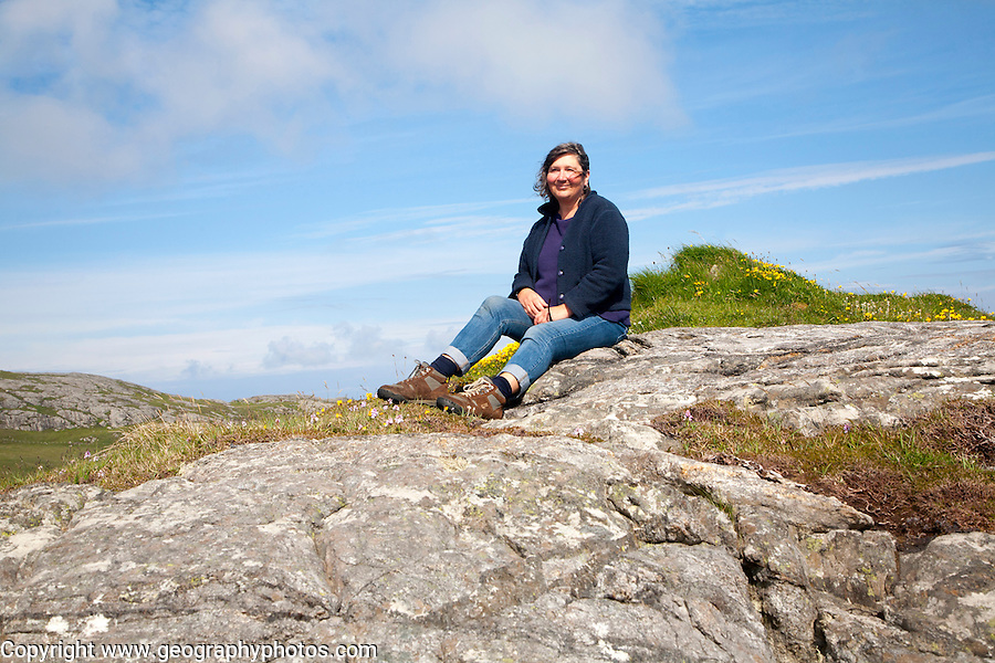 Middle aged female hiker sitting high on rocky outcrop in Barra, Outer Hebrides, Scotland, UK