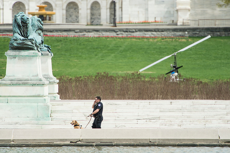 UNITED STATES - APRIL 15: A U.S. Capitol Police officer and his dog sweep the area around the reflecting pool on the west front of the Capitol after a man was arrested for landing a gyrocopter on the West Lawn of the U.S. Capitol on Wednesday, April 15, 2015. The small helicopter was painted with a U.S. Postal Service logo. (Photo By Bill Clark/CQ Roll Call)