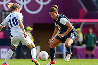 Glasgow, Scotland - July 25, 2012: Carli Lloyd and France's Camille Abily challenge a ball at the 2012 London Olympics. USA won 4-2.